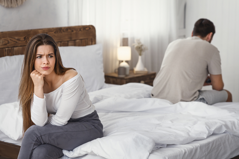 Angry couple sitting on opposite sides of bed
