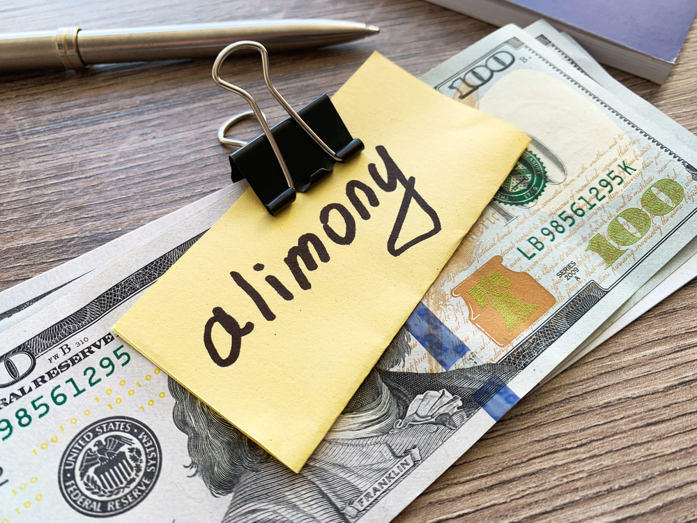 Stack of money clipped with paper labeled alimony