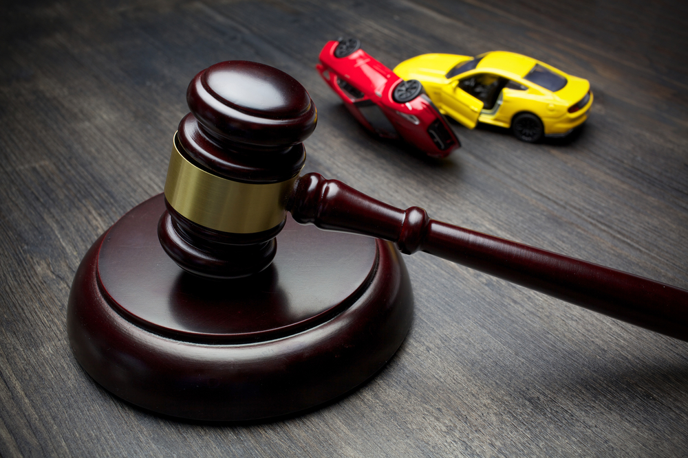 Judge's gavel and crashed toy cars