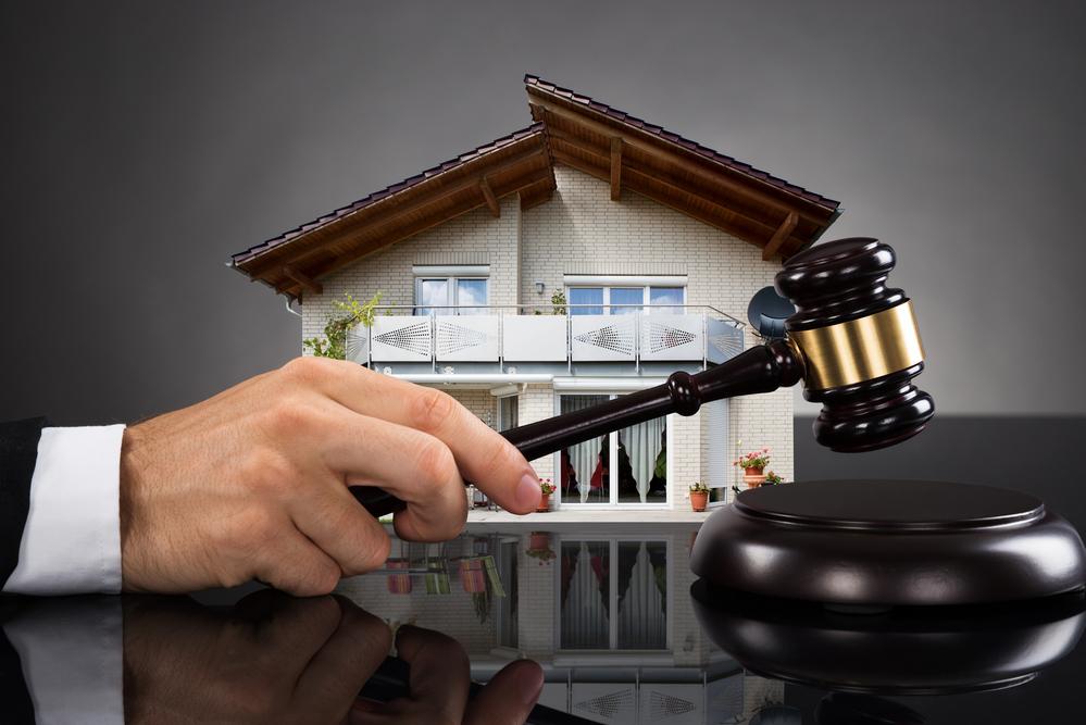Hand holding gavel near model of house