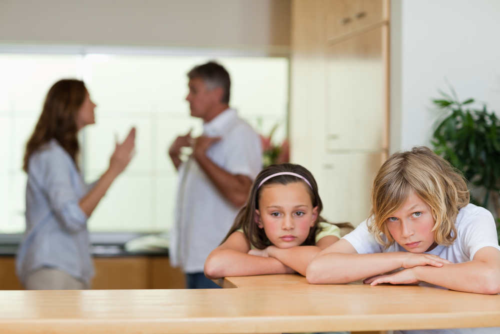 Upset children with parents fighting in background