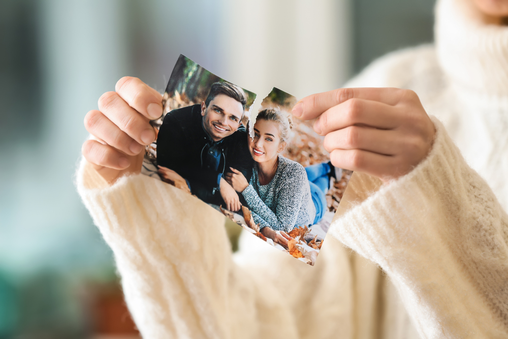 Woman ripping photo of couple