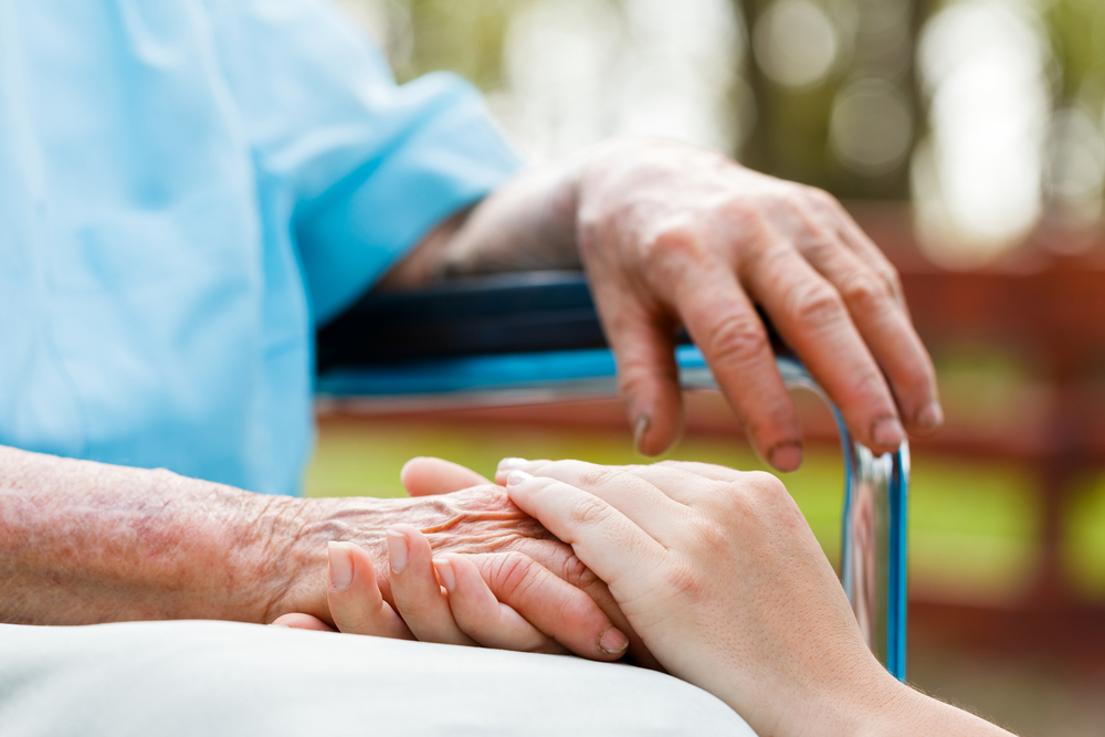 A younger hand holding an elderly hand extended from someone in a wheelchair outdoors