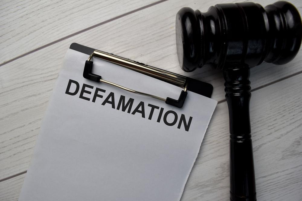 Defamation written on clipboard next to black gavel