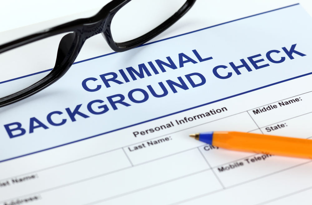 Application for criminal background check with glasses and pen