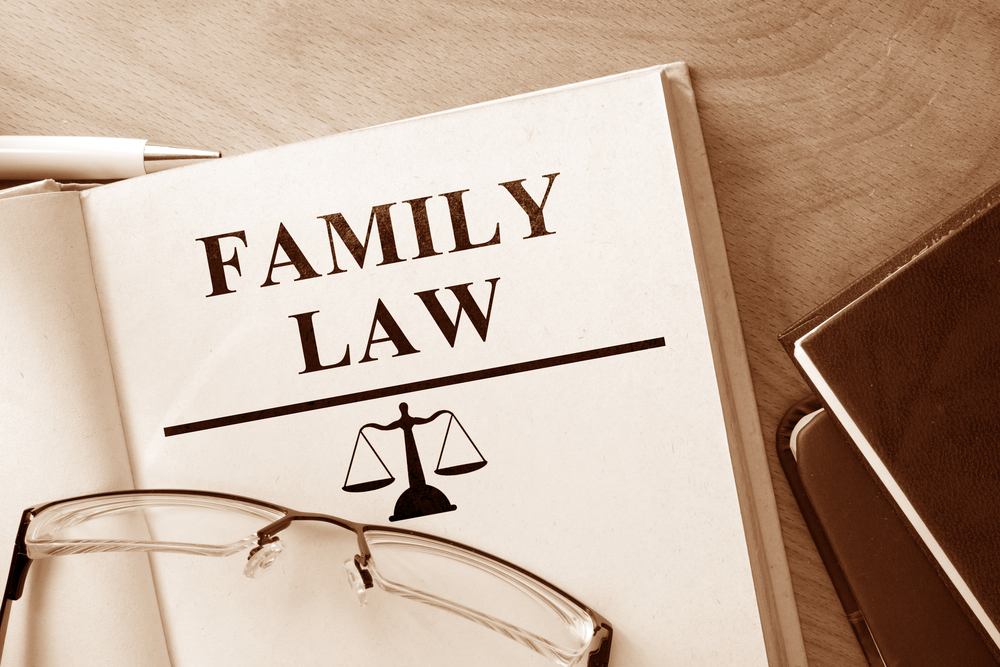 Open family law book with glasses set on top