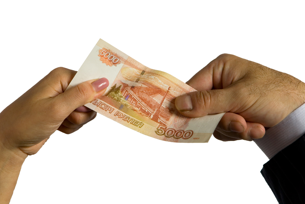 Man and woman's hands holding Russian bill