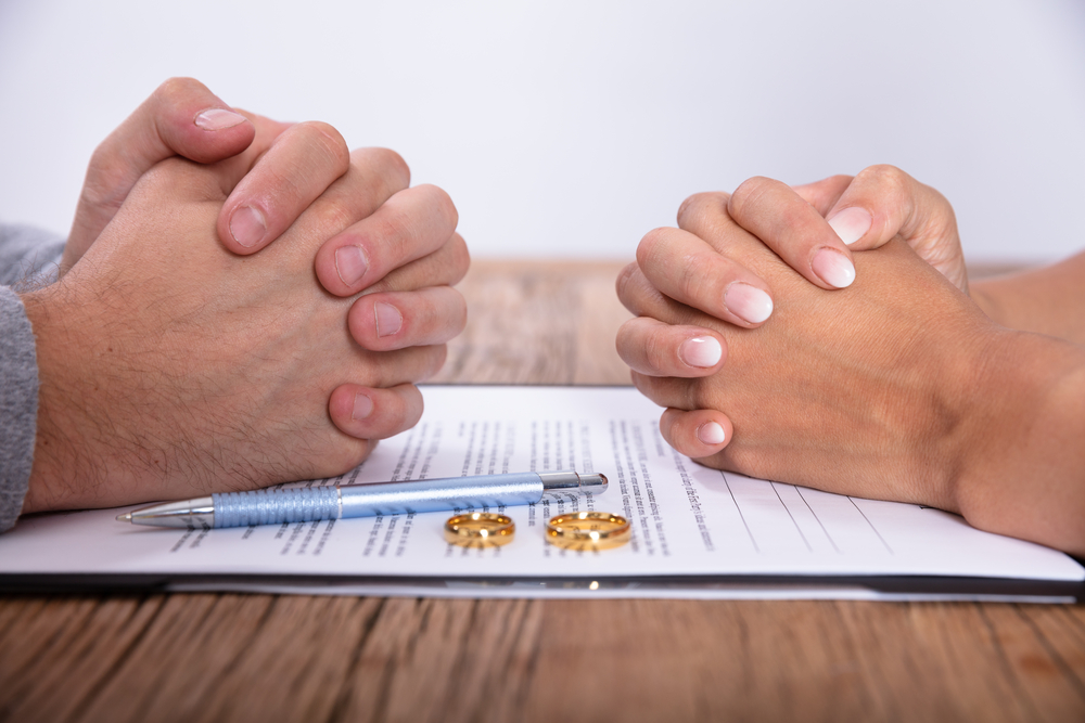 Couples' hands folded on paperwork beside wedding rings