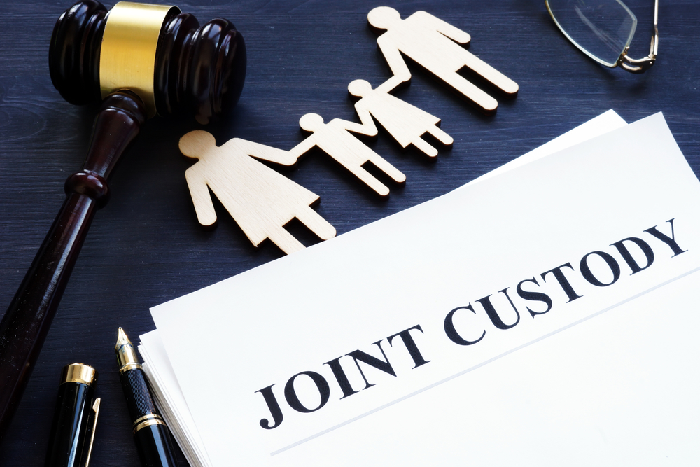 Joint custody papers with gavel and paper cutout of family