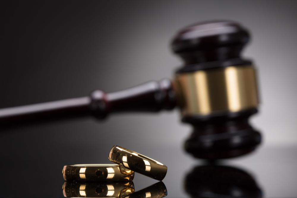 Judge gavel behind wedding bands