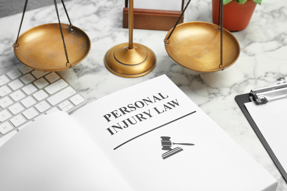 Personal injury lawbook near keyboard and scales