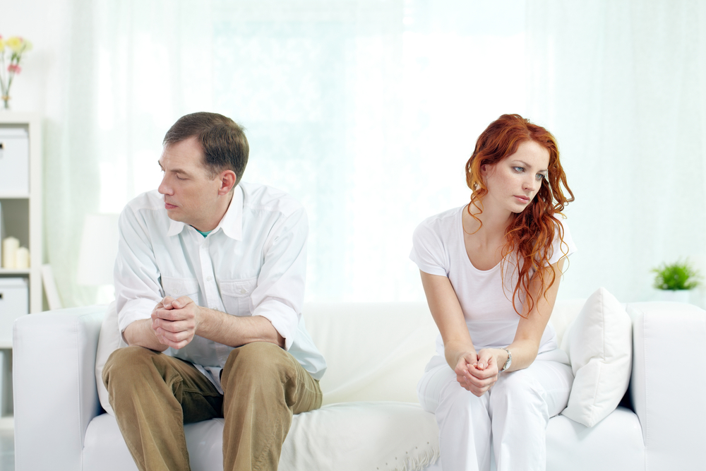 Upset couple sitting on sofa and looking away from each other