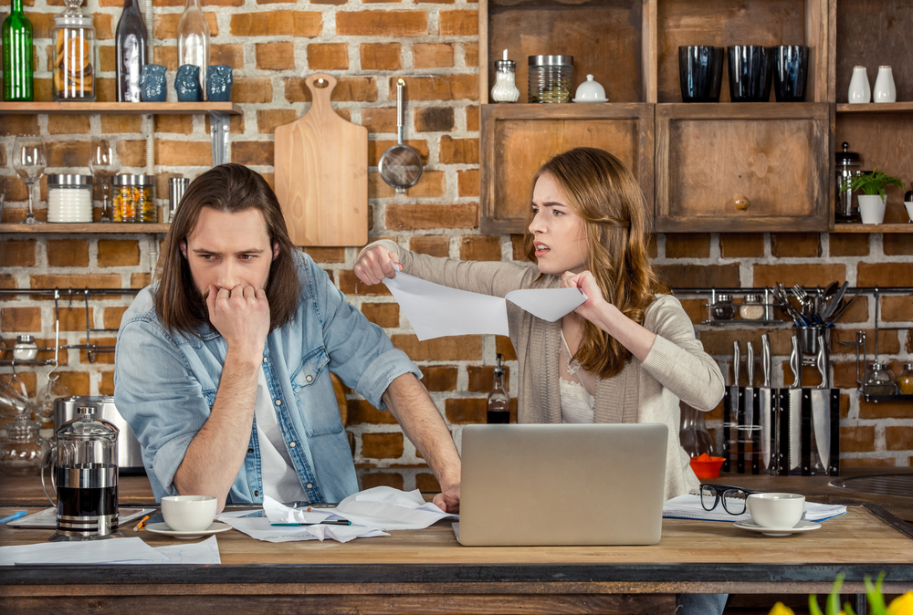 Woman ripping up pairs next to upset man