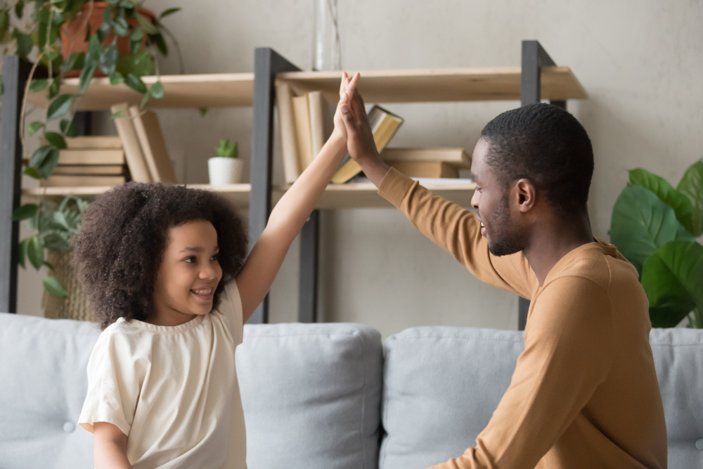 Stepdad and stepdaughter high-fiving on sofa