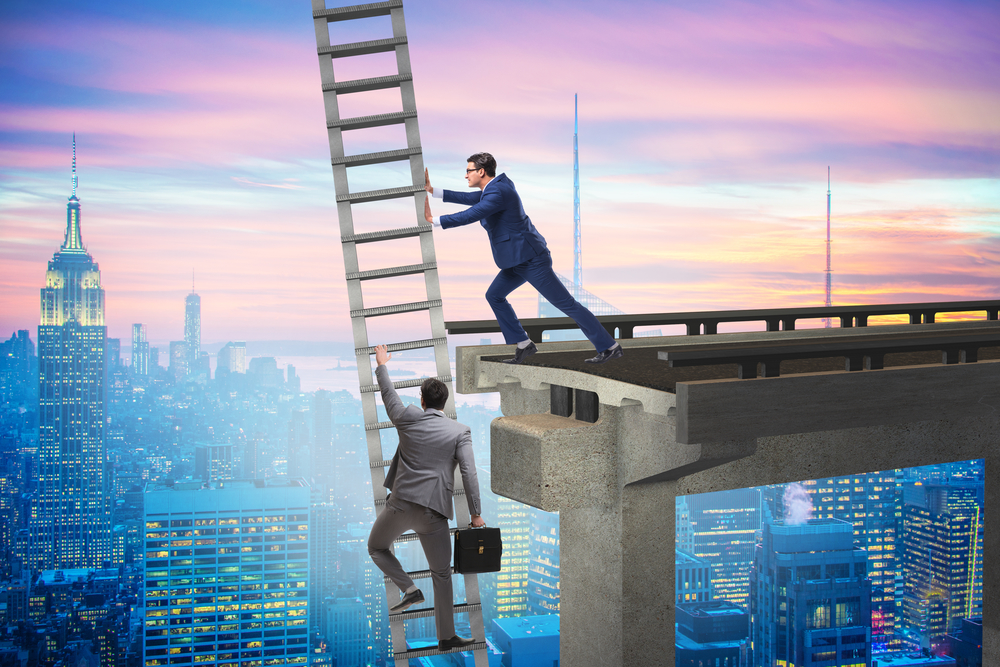 Businessman pushing over ladder while another tries to climb