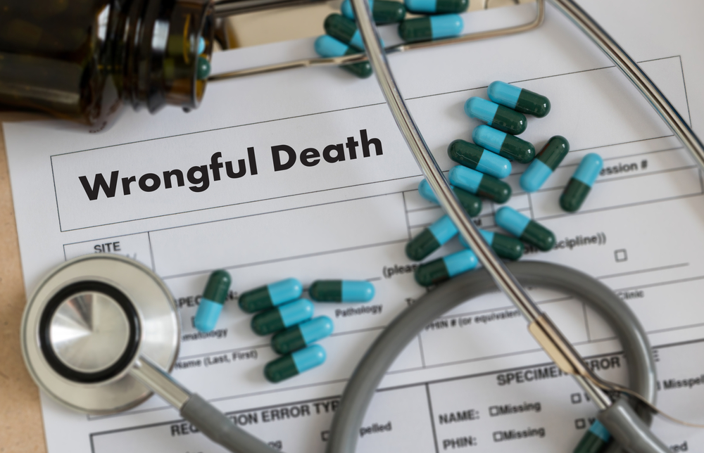 Stethoscope and pills atop wrongful death papers